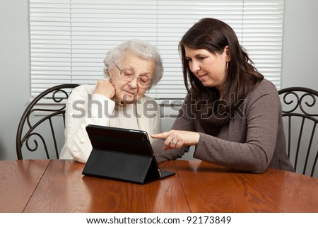 Young Woman Showing Senior Woman How to Use a Tablet PC