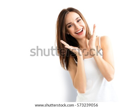 Young woman showing smile, in casual smart clothing, isolated against white background. Caucasian brunette model in emoshions and optimistic, positive, happy feeling concept studio shoot.
