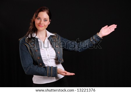 Young woman showing something on black