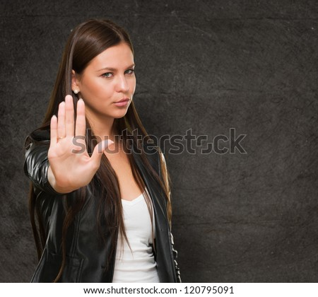 Young Woman Showing Stop Hand Gesture against a grunge background