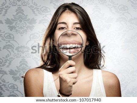 young woman showing teeth trough magnifying glass - stock photo