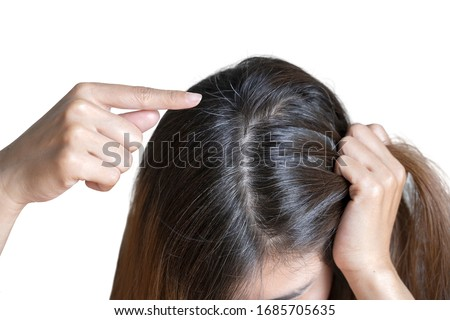 Young woman shows her black gray hair roots on white background ストックフォト ©