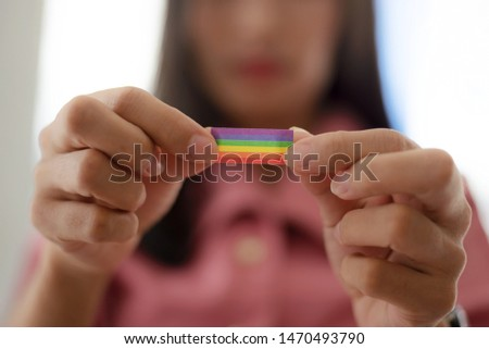 Young woman shows LGBT rainbow flag in her hands.