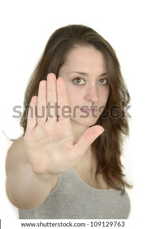 young woman shows open hand before white background, isolated, studio shot