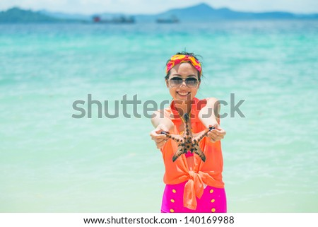 Young woman shows starfish during holiday at tropical island