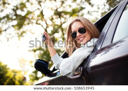 Young woman shows the keys to her new car