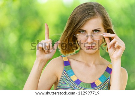 Young woman shows up with his finger, against green of summer park.