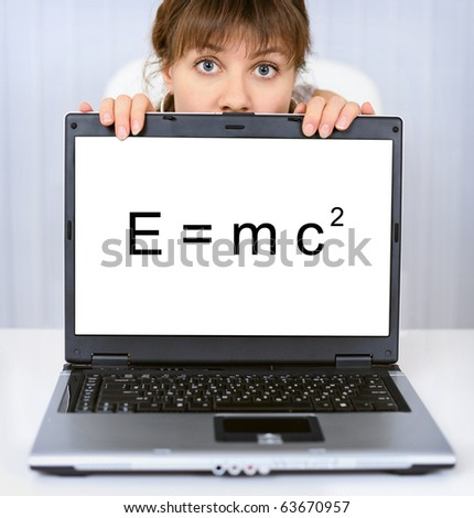 Young woman shows us a computer screen with formula - stock photo