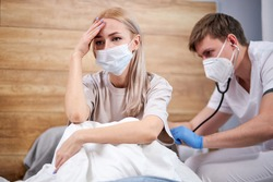 young woman sick of flu viral infection in home isolation quarantine, lie on bed while doctor is listening to breat using stethoscope. focus on blond female patient