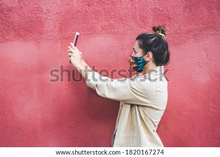 Young woman sideway taking a selfie with a smatphone and wearing a reusable mask against coronavirus. Close up view. Zdjęcia stock ©