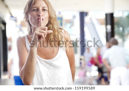 young woman silence gesture in a shopping center