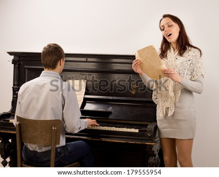 Young woman singing a solo song standing alongside a young man playing an upright piano singing with obvious enjoyment
