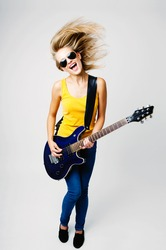 Young woman singing and playing on electric guitar
