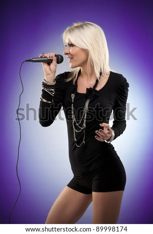 Young woman singing at microphone on purple background