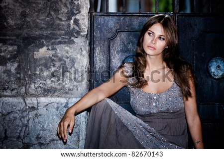 young woman sit in front of entrance gate on the street