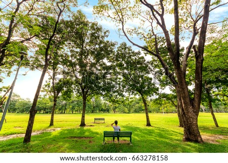 Young woman sit on bench in beautiful park scene in park with green grass field - Shutterstock ID 663278158
