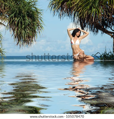 Young woman siting beside swimming pool on the beach - stock photo