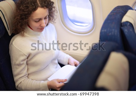 Young woman sits in a chair near the illuminator of the airplane and reads something.