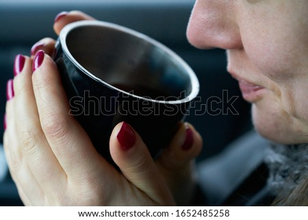 Young woman sits in the trunk of the car and holds a cup of hot drink in her hands