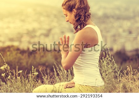 Young woman sits in yoga pose with city on background Freedom concept Calmness and relax woman happiness Toned image
