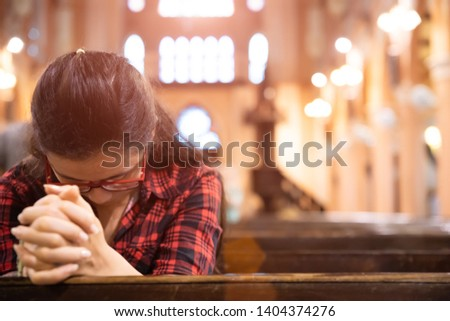Young woman sits on a bench in the church and prays to God. Hands folded in prayer concept for faith. #1404374276