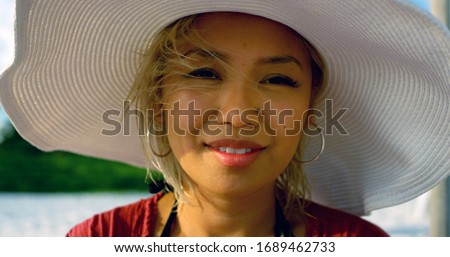 Young woman sits on the beach while on vacation enjoying the sun and surf wearing a beach hat, smiling and happy