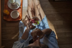 Young woman sits on the floor of a room while eating a bowl of fruit,  drinking a glass of orange juice and the sun coming through the window lights up your legs
