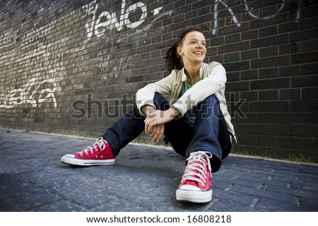 Young woman sitting against a brick wall