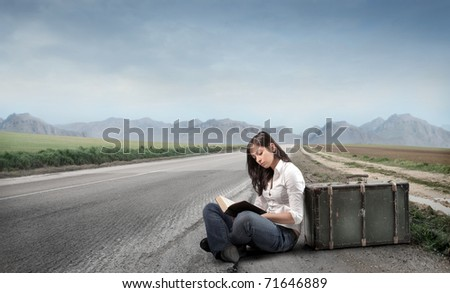 Young woman sitting against a suitcase on a countryside road and reading a map