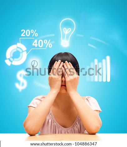 Young woman sitting against blue background with eyes closed by her hands. Business icons are flying around her head