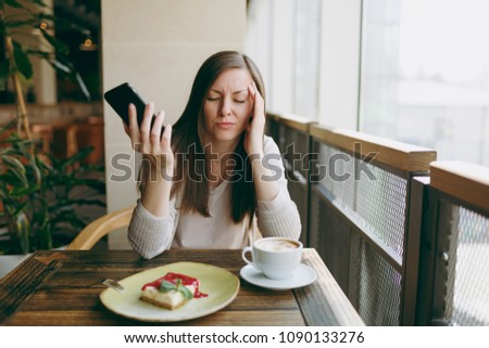 Young woman sitting alone in coffee shop at table with cup of cappuccino, cake, relaxing in restaurant during free time. Young female talking on mobile phone, having rest in cafe. Lifestyle concept #1090133276