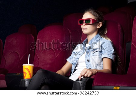 young woman sitting alone in the cinema and watching a movie