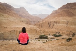 Young woman sitting and looking at desert valley.