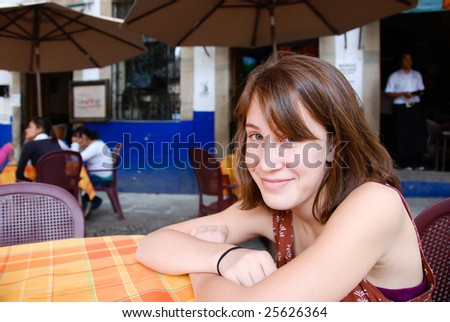 Young woman sitting at a table in an outdoor restaurant in Mexico.