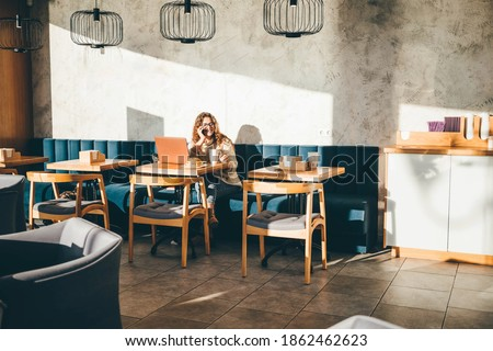 Young woman sitting at caffe, drinking coffee, working on laptop and talking at the phone. Foto d'archivio ©