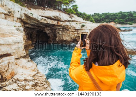 young woman sitting at cliff looking at grotto cave with blue azure water. taking picture. background
