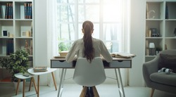 Young woman sitting at desk and studying at home, she is reading books, back view
