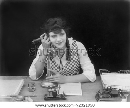 Young woman sitting at her desk in an office with a telephone in her hands