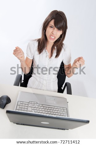 Young woman sitting at her desk with her laptop with a desperate expression