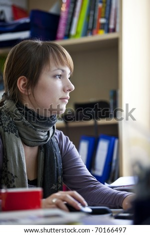 Young woman sitting at her office desk while she is working very concentrated with the computer.