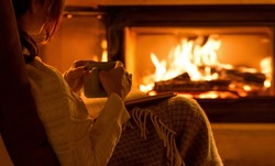 Young woman  sitting at home by the fireplace and reading a book.