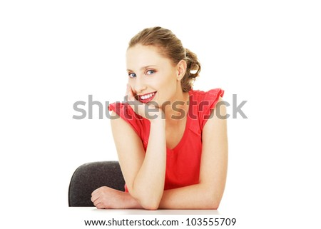 Young woman sitting at the desk, isolated on white background
