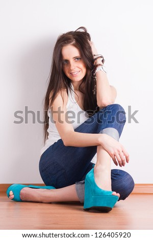 Young woman sitting at the floor. Studio shot.
