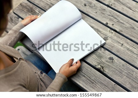 Young woman sitting at the table with a booklet with white pages. The white pages can be used for any logos, label signs or any graphic additions.