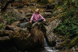 Young woman sitting barefoot on a big stone cross-legged, meditating, enjoying air and sound of running water. Over mountain spring with huge square boulders and autumn deciduous trees above.