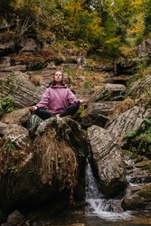 Young woman sitting barefoot on a big stone cross-legged, meditating. Over mountain spring with huge square boulders and autumn deciduous trees above.