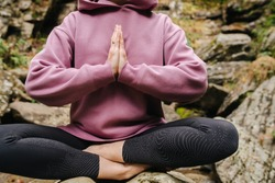 Young woman sitting barefoot on a big stone cross-legged, meditating. Over mountain spring with huge square boulders. Close up, cropped, no face, hands joined.