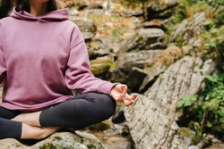 Young woman sitting barefoot on a big stone cross-legged, meditating. Over mountain spring with huge square boulders. Close up, cropped, no face.