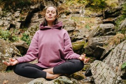 Young woman sitting barefoot on a big stone cross-legged, meditating. Over mountain spring with huge square boulders. Her eyes closed, fingers joined.
