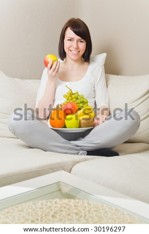 Young woman sitting cross-legged and eating fruits